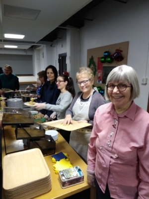 Joukko vapaaehtoistyöntekijöitä on ryhmittynyt pöydän taakse ruokaa tarjoilemaan