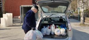 Ruokakasseja pakataan henkilöauton takakonttiin