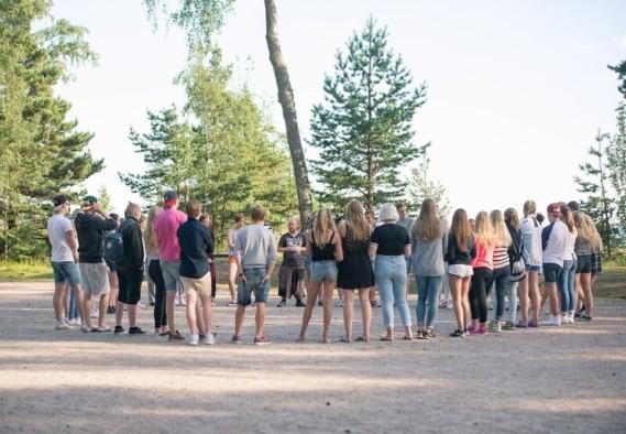 Joukko nuoria seisoo piirissä kuuntelemassa ohjaajan ohjeita
