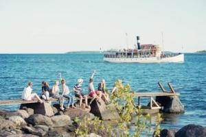 Nuoret istuvat laiturilla ja vilkuttavat ohiajavalle laivalle
