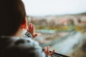 Pieni lapsi katsoo ulos ikkunasta kohti sateista maisemaa